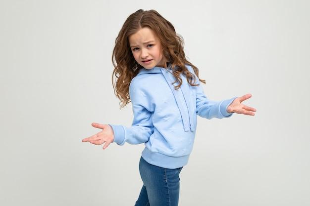 Menina adolescente bonito em um capuz azul indignado acenando as mãos sobre um fundo branco