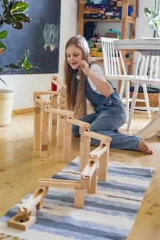 Menina adolescente brincando de construção de pista de torre com bola metálica maria montessori