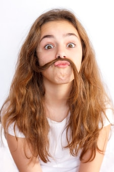 Menina adolescente brincando e fazendo um bigode do cabelo dela