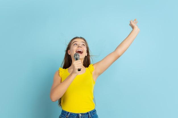Menina adolescente cantando como uma celebridade