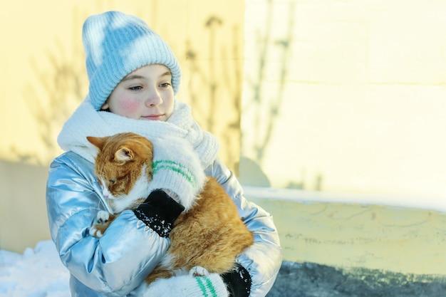 Menina adolescente carrega um gato sem-teto nas mãos num dia de inverno. cuidar de animais vadios.