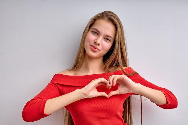 Menina adolescente caucasiana com sorriso fofo e cabelo comprido natural, vestindo roupas casuais, fazendo sha ...