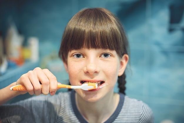 Menina adolescente caucasiana, escovando os dentes no banheiro.