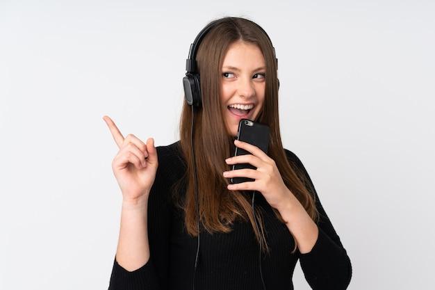 Menina adolescente caucasiano isolada na parede branca, ouvindo música com um celular e cantando