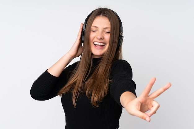 Menina adolescente caucasiano isolada na parede branca, ouvir música e cantar