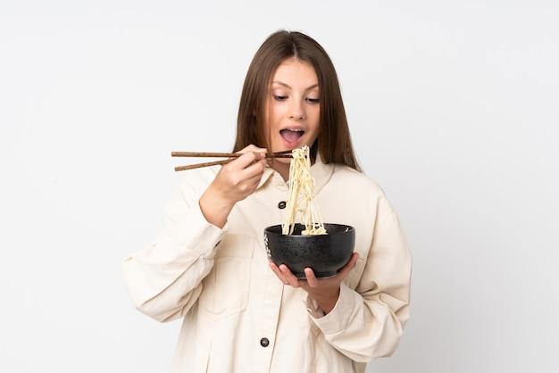 Menina adolescente caucasiano isolada no branco, segurando uma tigela de macarrão com pauzinhos e comê-lo