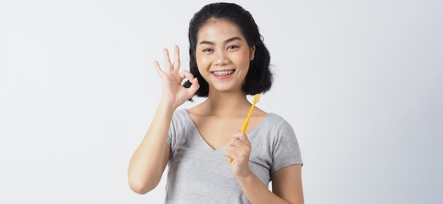 Menina adolescente cinta dentária sorriso segurando a escova de dentes. dentes brancos com aparelho azul. cuidado dental. mulher asiática com lentes de contato e acessórios ortodônticos. odontologia estética.