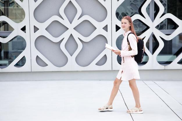 Menina adolescente colegial com livro sobre fundo de edifício de concreto com mochila nas costas cópia ...