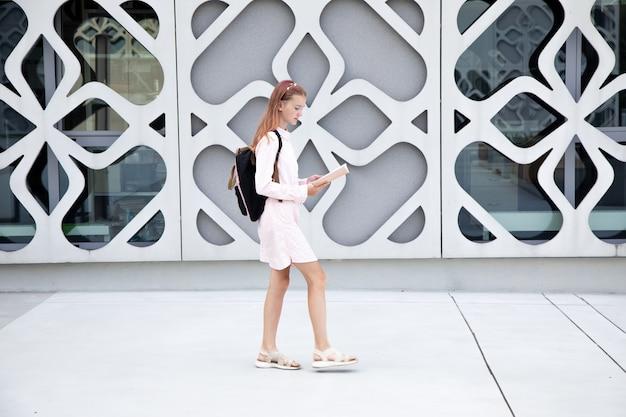 Menina adolescente colegial lê um livro em movimento contra o pano de fundo do edifício de concreto com backpac ...