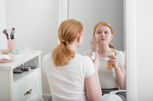 Menina adolescente coloca máscara facial