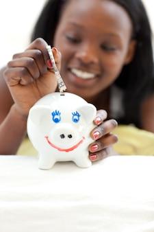 Menina adolescente colocando dinheiro em um piggybank