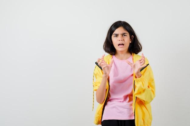 Menina adolescente com agasalho amarelo, camiseta mostrando garras imitando um gato e parecendo desconfiada, vista frontal.