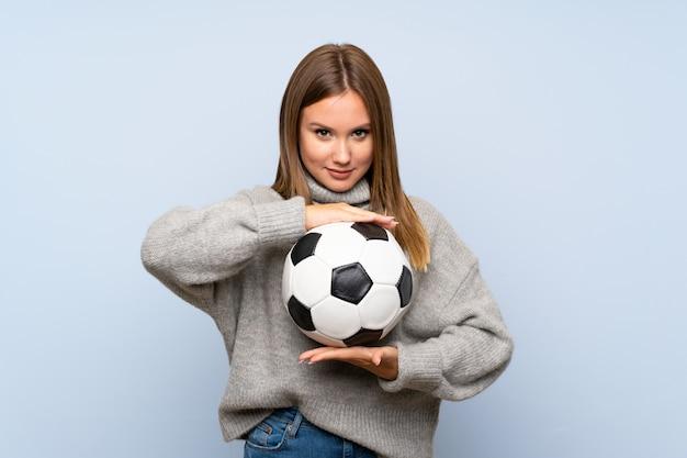 Menina adolescente com blusa sobre parede azul isolada, segurando uma bola de futebol
