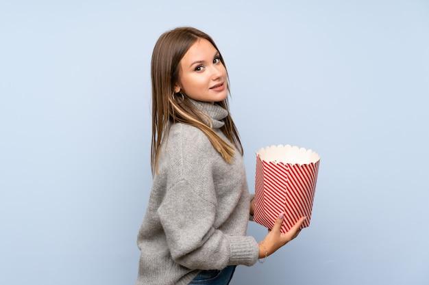 Menina adolescente com blusa sobre parede azul isolada, segurando uma tigela de pipocas