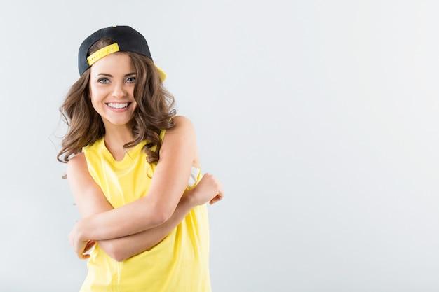Menina adolescente com boné e braços cruzados
