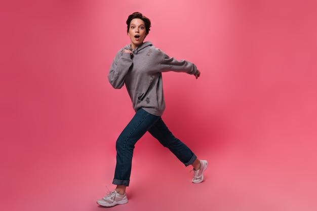 Menina adolescente com capuz olha para a câmera e se move no fundo rosa. uma linda mulher em calças jeans e moletom cinza caminha isolada