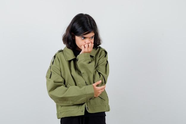 Menina adolescente com casaco verde, segurando a mão na boca e olhando com medo, vista frontal.