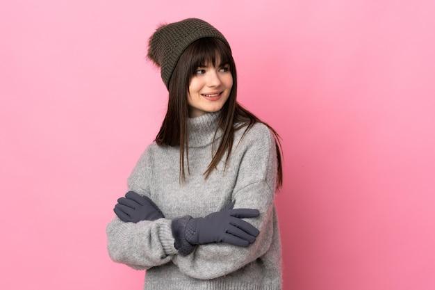 Menina adolescente com chapéu de inverno isolada no branco olhando para o lado
