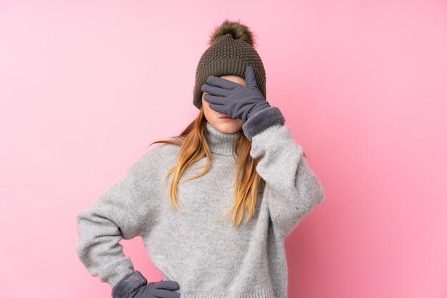 Menina adolescente com chapéu de inverno sobre rosa isolado