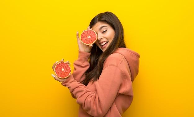 Menina adolescente, com, cor-de-rosa, sweatshirt, ligado, experiência amarela, com, laranjas