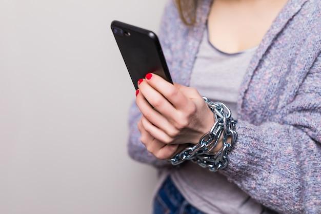 Menina adolescente com corrente de mãos presas usando um smartphone isolado