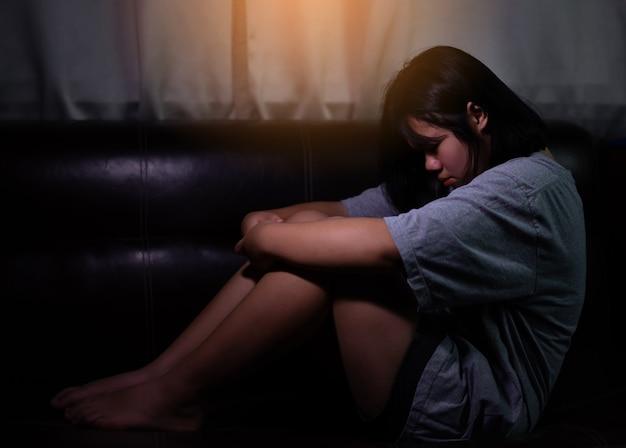 Menina adolescente com depressão ou triste sentada sozinha no quarto escuro. transtorno depressivo maior. conceito solitário e problemas de saúde.