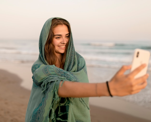 Menina adolescente, com, echarpe verde, cabeça, levando, retrato ego, em, praia