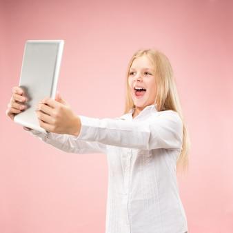 Menina adolescente com laptop. amo o conceito de computador. retrato feminino atraente com metade do corpo, fundo rosa moderno