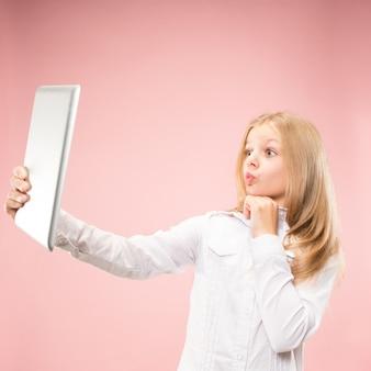 Menina adolescente com laptop. amo o conceito de computador. retrato frontal feminino atraente com metade do comprimento, moderno estúdio rosa backgroud. emoções humanas, conceito de expressão facial.