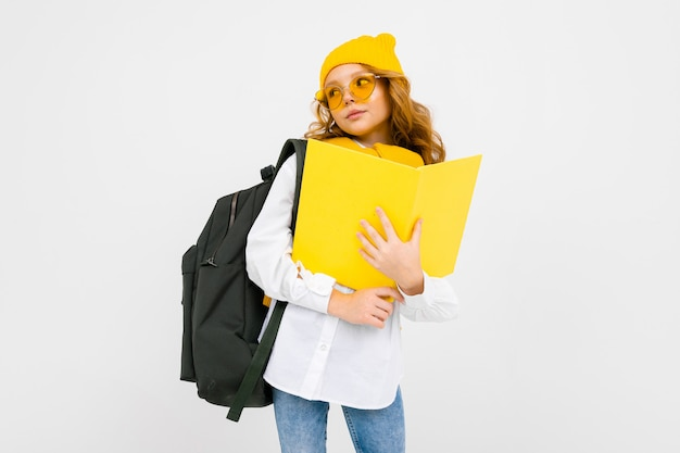 Menina adolescente com livros na mão e uma mochila nos ombros em um branco isolado