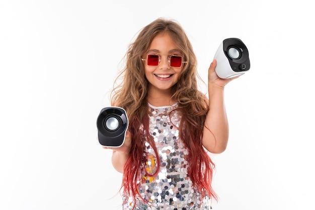 Menina adolescente com longos cabelos loiros tingidos com dicas-de-rosa, em vestido claro brilhante, tênis preto e branco, óculos, em pé com fones de ouvido, segurando colunas musicais nas mãos