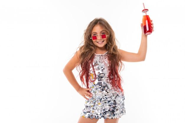 Menina adolescente com longos cabelos loiros tingidos com dicas-de-rosa, em vestido claro brilhante, tênis preto e branco, óculos, em pé com fones de ouvido, segurando o suco em frasco de vidro com tubo listrado na mão