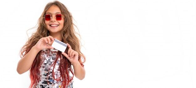 Menina adolescente com longos cabelos loiros tingidos com dicas-de-rosa, em vestido claro brilhante, tênis preto e branco, óculos, em pé com fones de ouvido, segurando um cartão nas mãos