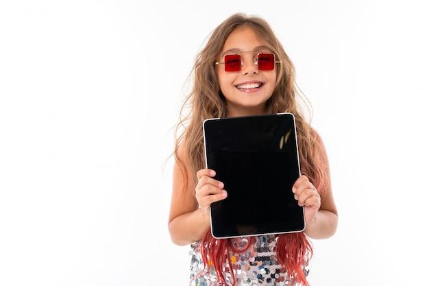 Menina adolescente com longos cabelos loiros tingidos com dicas-de-rosa, em vestido claro brilhante, tênis preto e branco, óculos, em pé com fones de ouvido, segurando um tablet nas mãos