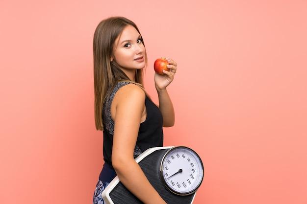 Menina adolescente com máquina de pesagem sobre fundo isolado