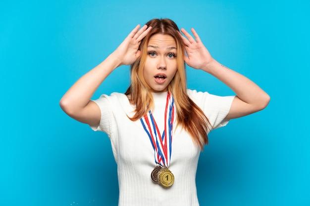 Menina adolescente com medalhas em fundo isolado com expressão de surpresa