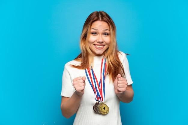 Menina adolescente com medalhas na parede isolada comemorando vitória na posição de vencedora
