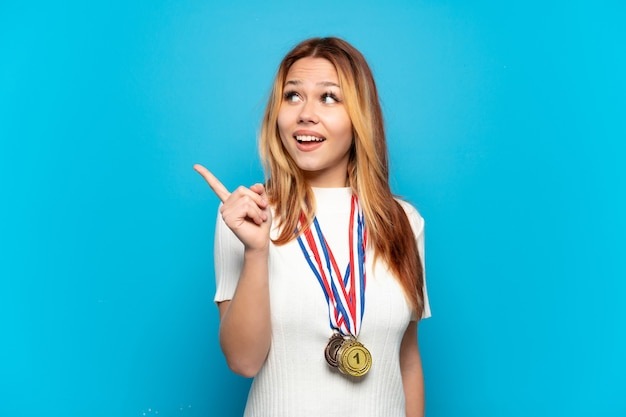 Menina adolescente com medalhas sobre fundo isolado com a intenção de descobrir a solução enquanto levanta um dedo
