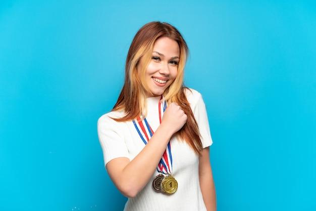 Menina adolescente com medalhas sobre fundo isolado comemorando vitória