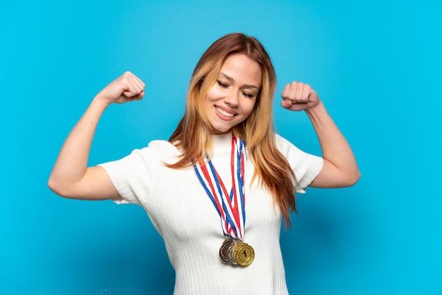 Menina adolescente com medalhas sobre fundo isolado fazendo gestos fortes