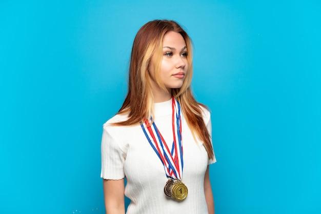 Menina adolescente com medalhas sobre fundo isolado olhando para o lado