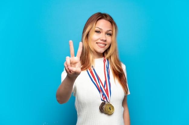 Menina adolescente com medalhas sobre fundo isolado sorrindo e mostrando sinal de vitória