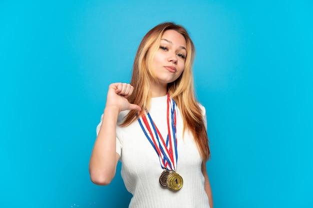 Menina adolescente com medalhas sobre um fundo isolado orgulhosa e satisfeita