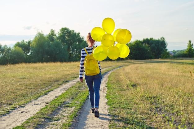 Menina adolescente com mochila e balões amarelos correndo na estrada secundária, vista traseira. garota feliz caminhando para frente, céu nas nuvens, prado, fundo da natureza