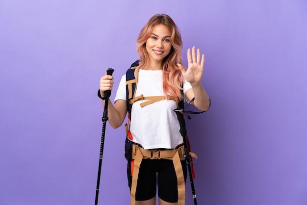 Menina adolescente com mochila e bastões de trekking na parede roxa isolada, contando cinco com os dedos