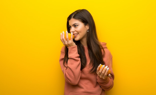 Menina adolescente com moletom rosa sobre fundo amarelo com laranjas