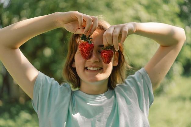 Menina adolescente com morango em uma camiseta em um ambiente ao ar livre e olhando para as pessoas da câmera e lifest ...
