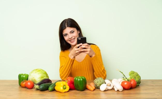 Menina adolescente com muitos legumes, enviando uma mensagem com o celular