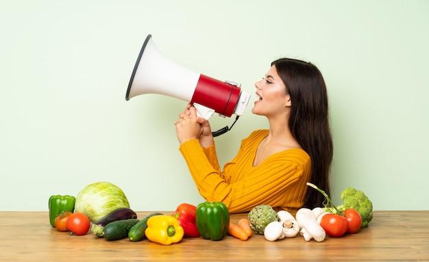 Menina adolescente com muitos legumes gritando através de um megafone