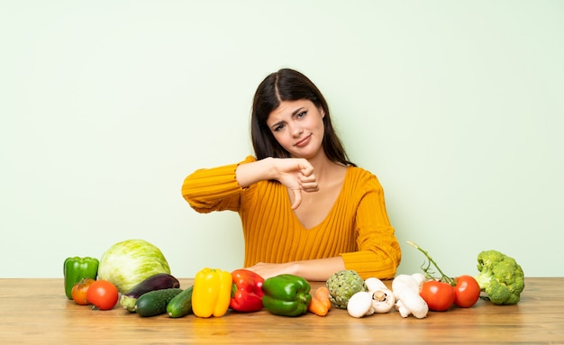 Menina adolescente com muitos legumes, mostrando o polegar para baixo com expressão negativa